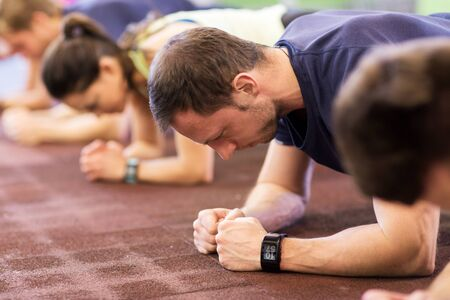 man with heart-rate tracker exercising in gym Stock Photo