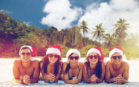 friends in santa hats on beach at christmas