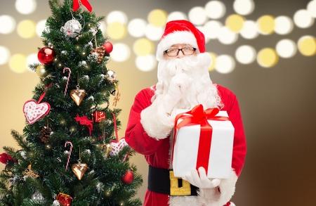saint nicolas: santa claus with gift box at christmas tree