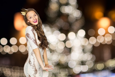 happy woman in crown over christmas tree lights