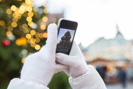 크리스마스 트리를 촬영하는 스마트 폰 손
