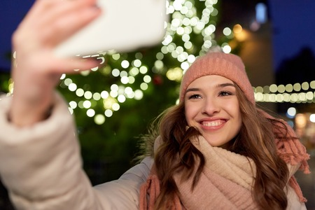 young woman taking selfie over christmas tree Stock Photo
