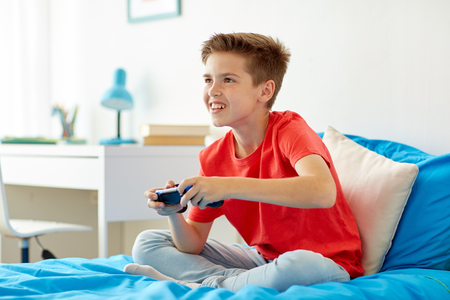 happy boy with gamepad playing video game at home Standard-Bild