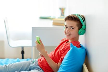 gelukkige jongen met smartphone en hoofdtelefoons thuis