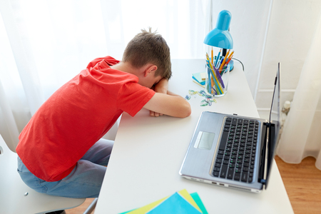 집에서 노트북과 피곤하거나 슬픈 학생 소년 스톡 콘텐츠