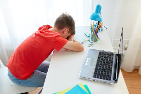 Moe of verdrietig student jongen met laptop thuis Stockfoto - 88171053