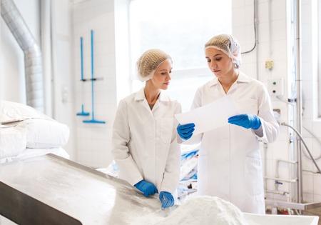 women technologists working at ice cream factory Foto de archivo