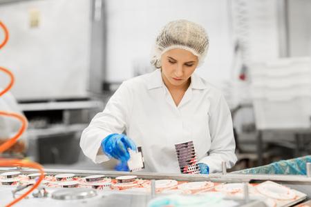woman working at ice cream factory conveyor 스톡 콘텐츠
