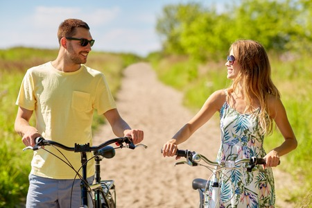 happy couple with bicycles on country road Stock Photo