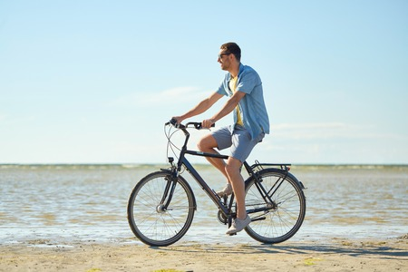 夏のビーチに沿って幸せな男乗って自転車