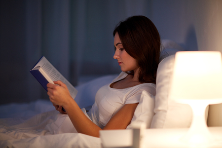 young woman reading book in bed at night home