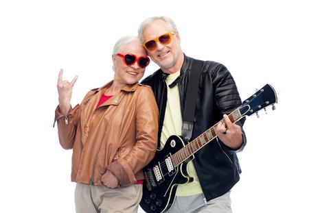 ロックハンドサインを示すギターを持つシニアカップル 写真素材