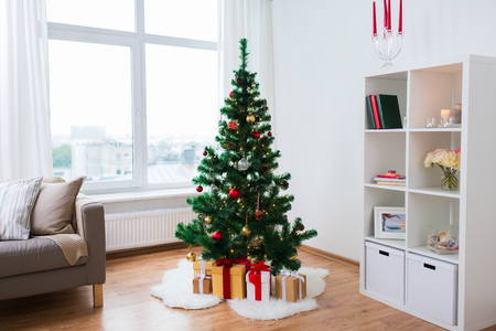 artificial christmas tree and presents at home Archivio Fotografico