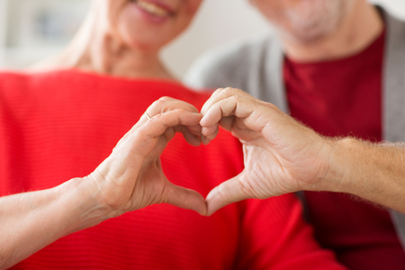 close up of senior couple showing hand heart sign