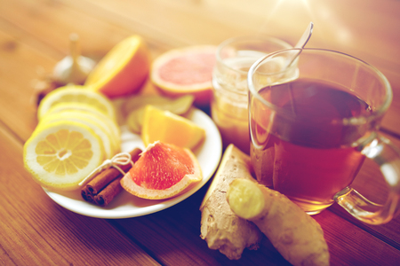indigenous medicine: ginger tea with honey, citrus and cinnamon on wood