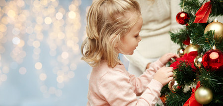 close up of little girl decorating christmas tree