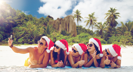 group of friends in santa hats with taking selfie Stock Photo
