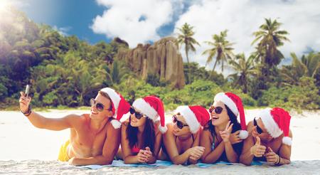 group of friends in santa hats with taking selfie Foto de archivo