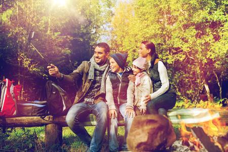 family with smartphone taking selfie near campfire Фото со стока