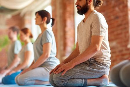 group of people doing yoga kneeling pose at studio Stock Photo