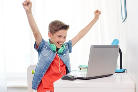 boy with headphones playing video game on laptop