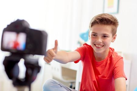 Ragazzo felice con la videocamera di registrazione video a casa