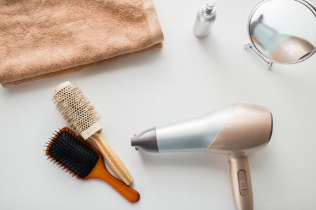 haardroger, haarborstels, spiegel en handdoek Stockfoto