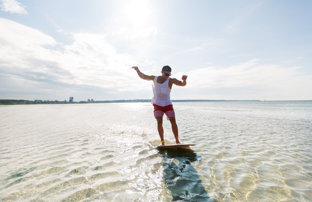 young man riding on skimboard on summer beach