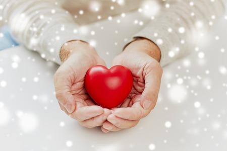 close-up van senior man met rood hart in handen