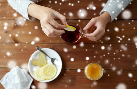 close up of ill woman adding lemon to tea cup Stock Photo
