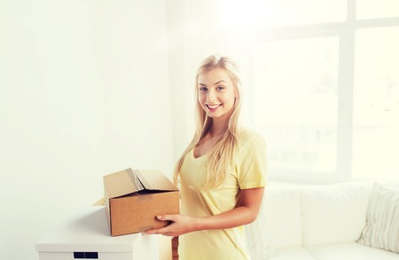 smiling young woman with cardboard box at home Stock Photo