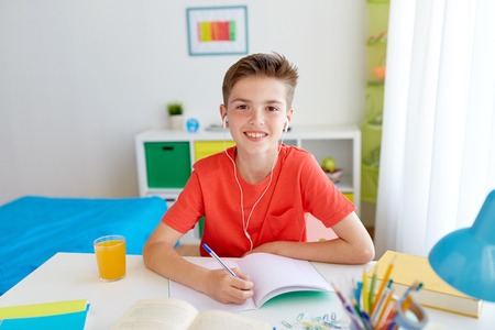 happy student boy writing to notebook at home Stock Photo