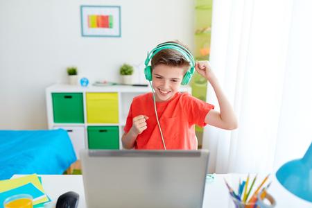 Jongen in hoofdtelefoon spelen video game op laptop