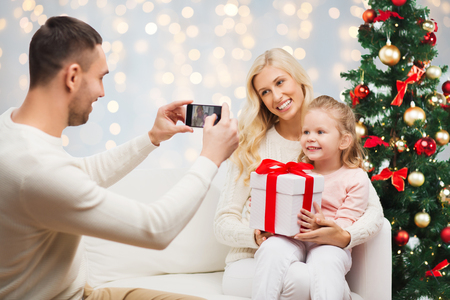 man photographing his family with christmas gift Stock Photo