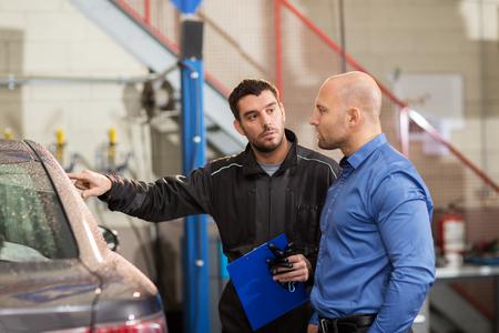 auto mechanic and customer at car shop Stock Photo