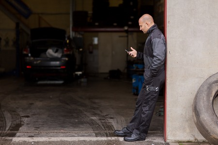 auto mechanic with smartphone at car service