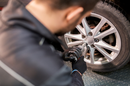 auto mechanic with screwdriver changing car tire