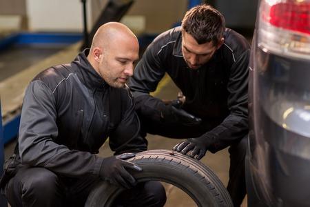 auto mechanics changing car tires at workshop