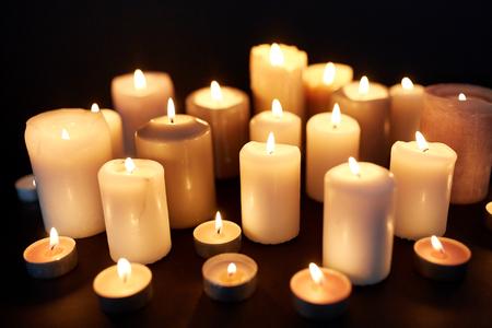 candles burning in darkness over black background 版權商用圖片