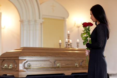 people and mourning concept - woman with red roses and coffin at funeral in church Stock Photo - 88451161