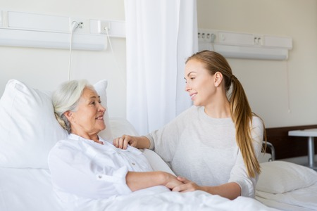 daughter visiting senior mother at hospital