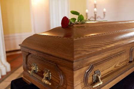 begrafenis en rouw concept - rode roos bloem op houten kist in de kerk