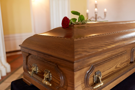 funeral and mourning concept - red rose flower on wooden coffin in church Stock Photo
