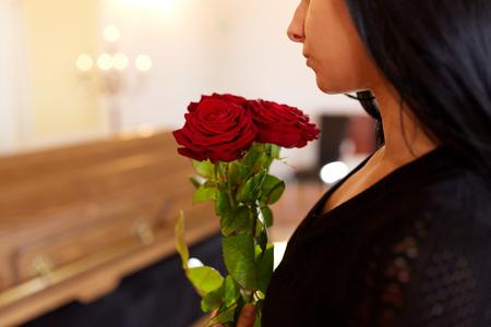 mensen en rouwconcept - vrouw met rode rozen en kist bij begrafenis in de kerk Stockfoto