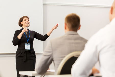 business, education and people concept - smiling businesswoman or lecturer with microphone talking to group of students at conference presentation or lecture