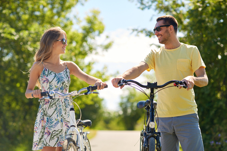 people, leisure and lifestyle concept - happy young couple with bicycles on country road Stock Photo