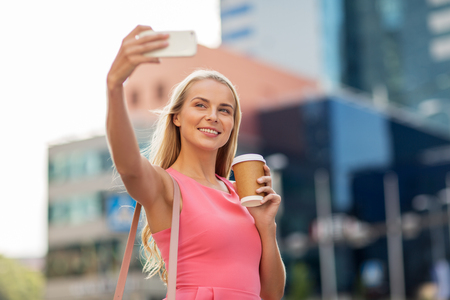technologie, levensstijl en mensenconcept - gelukkige glimlachende jonge vrouw met koffie en smartphone die selfie op stadsstraat nemen Stockfoto