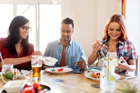 leisure, food and people concept - group of happy international friends eating at restaurant table Stock Photo