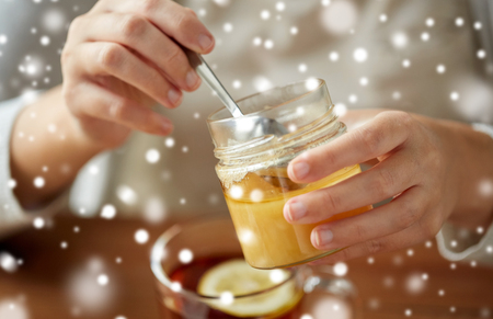 indigenous medicine: close up of woman adding honey to tea with lemon