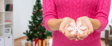 close up of woman hands with christmas snowflake Stock Photo